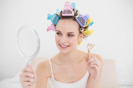 Beautiful natural brown haired woman in hair curlers looking herself in a mirror in bright bedroom photo