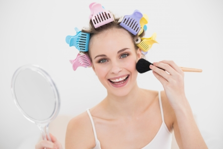 Smiling natural brown haired woman in hair curlers applying powder on her face in bright bedroom photo