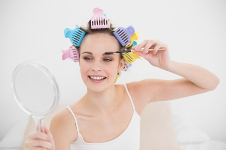 Attractive natural brown haired woman in hair curlers applying mascara in bright bedroom photo