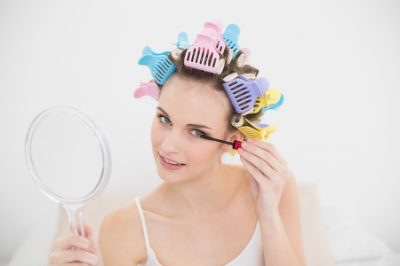 Beautiful natural brown haired woman in hair curlers applying mascara in bright bedroom photo