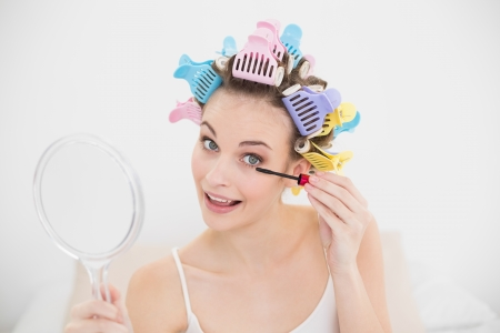 Cheerful natural brown haired woman in hair curlers applying mascara in bright bedroom photo