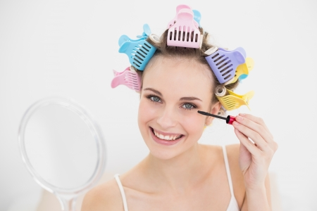 Pretty natural brown haired woman in hair curlers applying mascara in bright bedroom photo