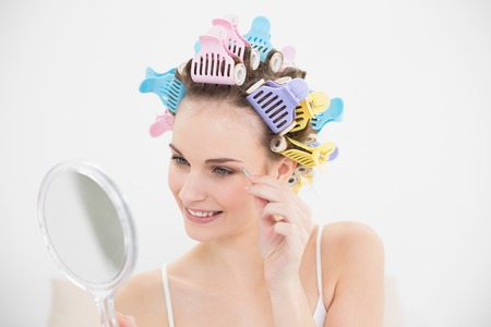 Cute natural brown haired woman in hair curlers plucking her eyebrows in bright bedroom photo
