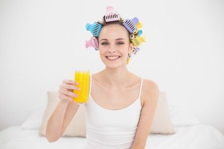 hair curlers: Charming natural brown haired woman in hair curlers holding a glass of orange juice in bright bedroom Stock Photo