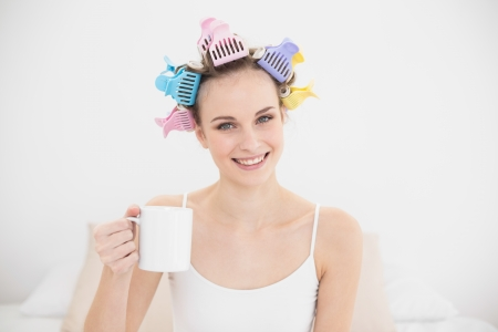 hot rollers: Amused natural brown haired woman in hair curlers holding a mug of coffee in bright bedroom Stock Photo