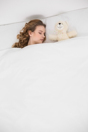 Pretty brunette sleeping next to teddy bear in bed photo
