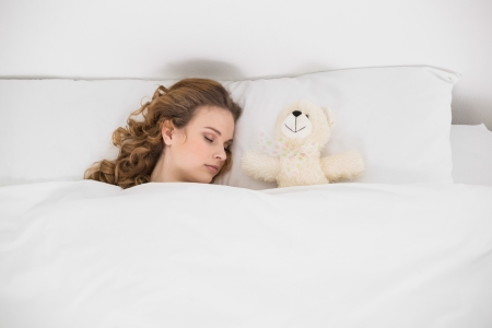 Attractive brunette sleeping next to teddy bear in bed photo