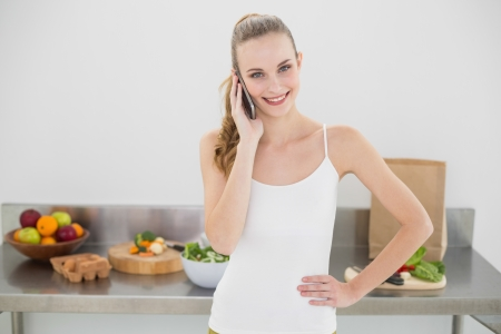 Pretty smiling woman phoning in bright kitchen photo