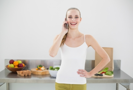 Pretty cheerful woman phoning in bright kitchen photo