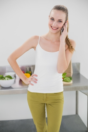 Pretty smiling woman phoning and standing with hand on hips in bright kitchen photo
