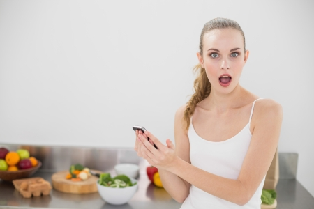 Shocked young woman holding smartphone looking at camera in the kitchen at home photo
