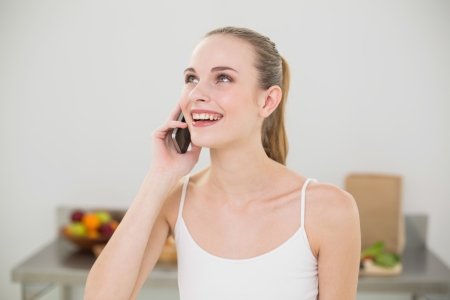 Happy young woman talking on smartphone in the kitchen at home photo