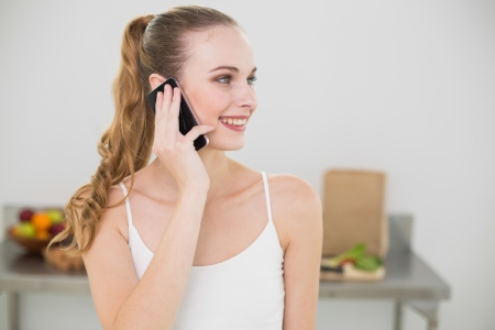 Smiling young woman talking on smartphone in the kitchen at home photo