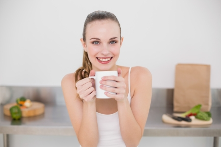 Happy young woman holding mug in the kitchen at home photo