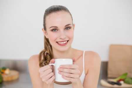 Cheerful young woman holding mug in the kitchen at home photo