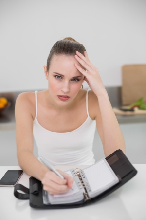 Stressed young woman writing in a planner looking at camera in the kitchen at home photo