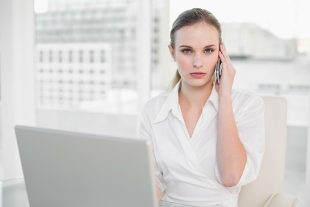 Frowning businesswoman using laptop and making a call in her office photo