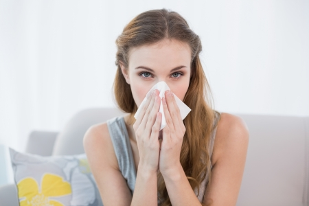 Sick young woman sitting on sofa blowing her nose at home in the sitting room Stock Photo - 25453127