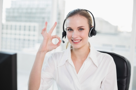 Happy call centre agent looking at camera giving ok sign in her office photo