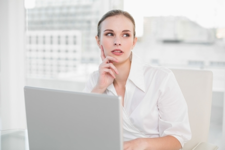 Thoughtful businesswoman using laptop in her office photo