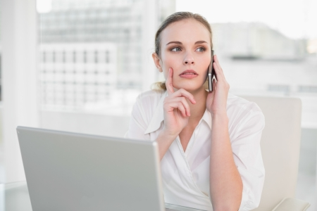 Thoughtful businesswoman using laptop and making a call in her office photo