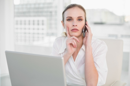 Thoughtful businesswoman using laptop and making a call looking at camera in her office photo