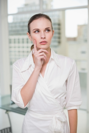 Thoughtful businesswoman standing in her office photo