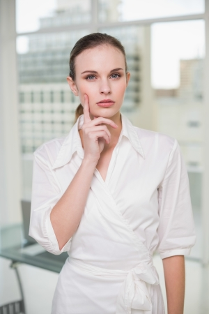Thoughtful businesswoman looking at camera in her office photo