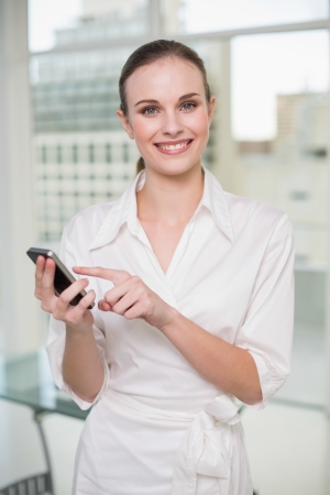 Smiling businesswoman using her smartphone in her office photo