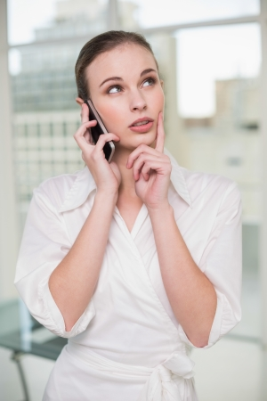Thoughtful businesswoman making a call on her smartphone in her office photo