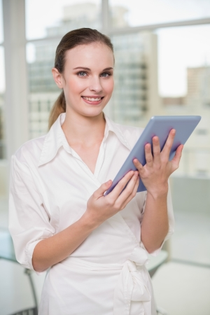 Happy businesswoman holding her tablet pc in her office photo