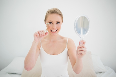 Natural happy blonde holding mirror and using eyelash curler in bright bedroom photo