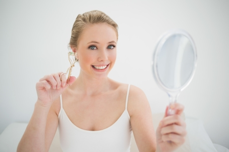 Natural smiling blonde holding mirror and eyelash curler in bright bedroom photo
