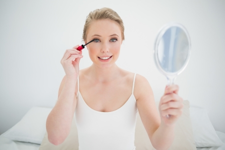 Natural smiling blonde holding mirror and applying mascara on bright bedroom photo