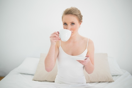 Natural content blonde drinking from a cup in bright bedroom photo