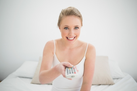 Natural smiling blonde holding remote while sitting on bed in bright bedroom photo