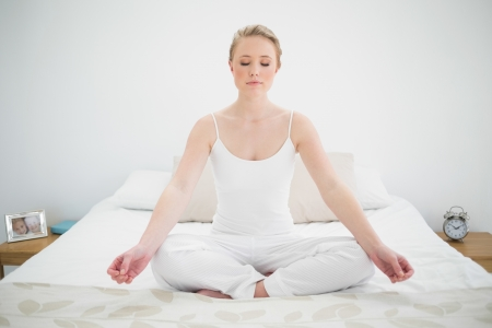 yoga pillows: Natural pretty blonde meditating on bed with closed eyes in bright bedroom