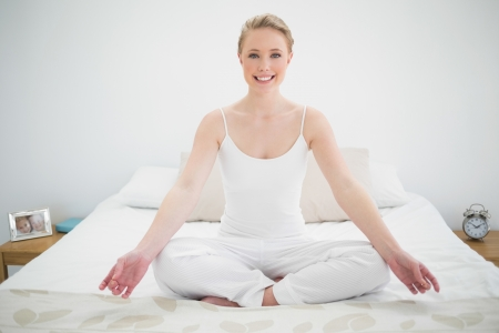 yoga pillows: Natural smiling blonde meditating on bed in bright bedroom