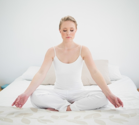 yoga pillows: Natural peaceful blonde meditating on bed in bright bedroom