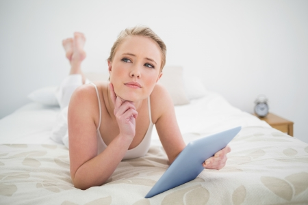 Natural thoughtful blonde lying on bed holding tablet in bright bedroom photo