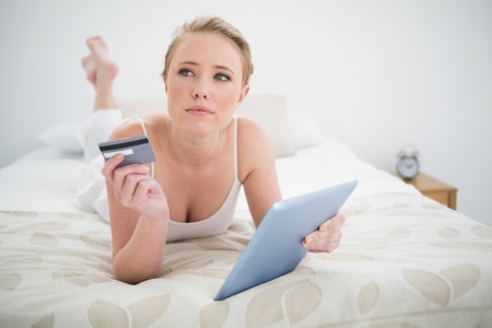 Natural thoughtful blonde lying on bed holding tablet and credit card in bright bedroom photo