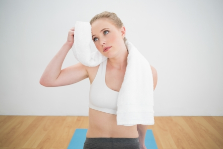Thoughtful sporty blonde touching forehead with towel in bright room photo