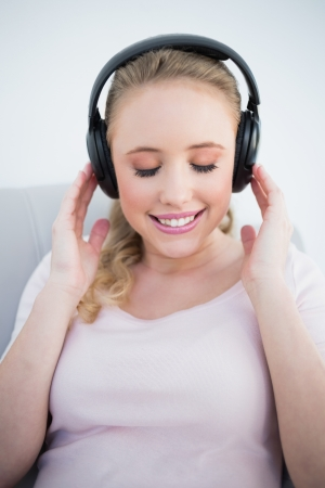 Casual smiling blonde listening to music with closed eyes in bright living room photo