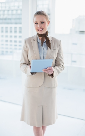 Blonde smiling businesswoman holding tablet in bright office photo