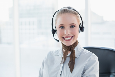 Blonde smiling businesswoman wearing a headset in bright office photo