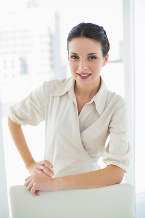 Smiling stylish brunette businesswoman posing looking at camera in bright office photo