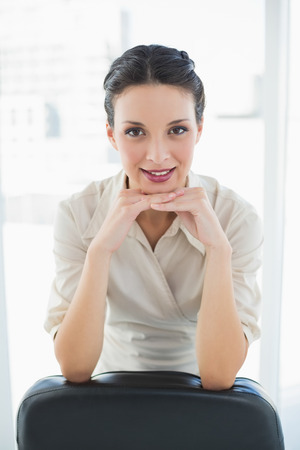 Happy stylish brunette businesswoman posing looking at camera in bright office photo