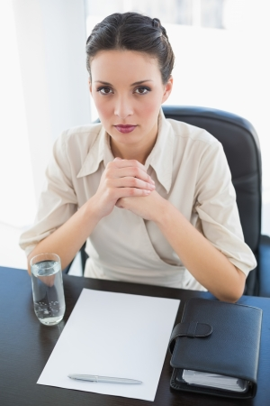 Stern stylish brunette businesswoman joining her hands and looking at camera in bright office photo