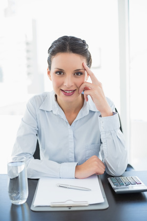Pleased stylish brunette businesswoman looking at camera and touching her face in bright office photo