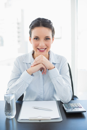 Happy stylish brunette businesswoman joining her hands and looking at camera in bright office photo
